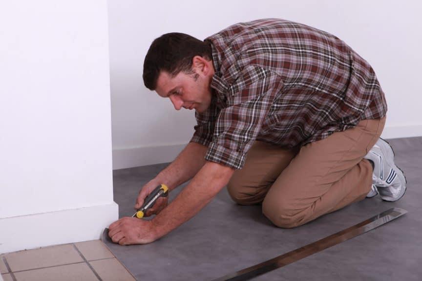 Man Laying Carpet Over Tiles